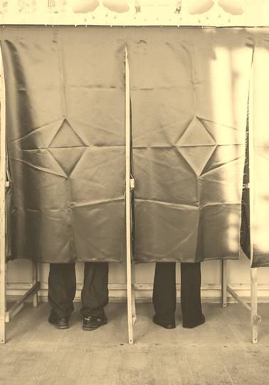 People at polling station voting behind curtain